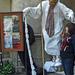 élő szobor - a lányok távozásakor, nádpálcájával megpaskolja a
